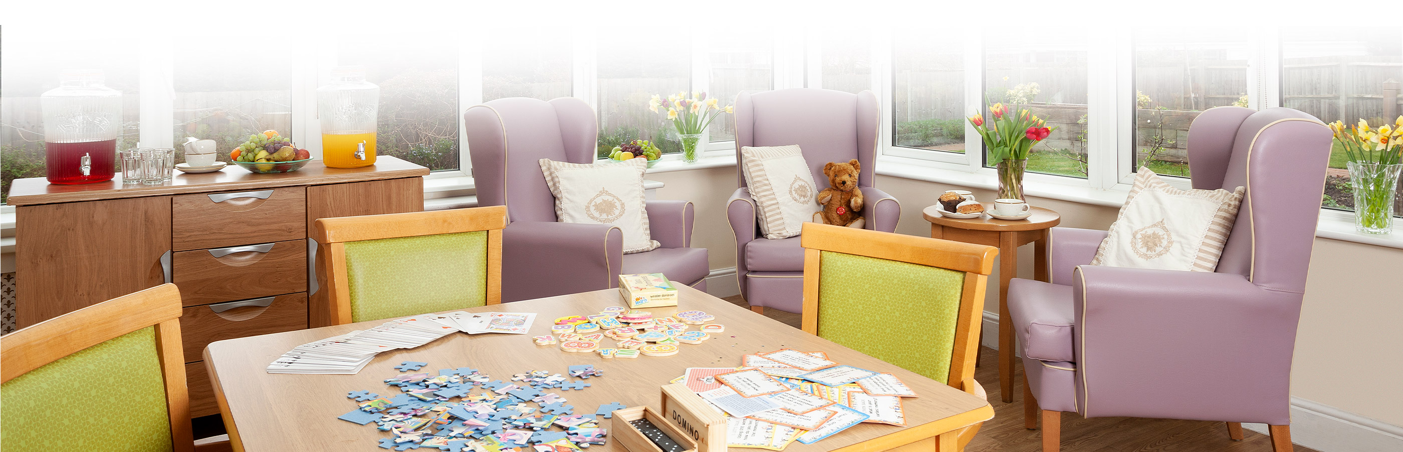 Living room with green and purple chairs and card games on table at Hamilton Nursing Home Surbiton