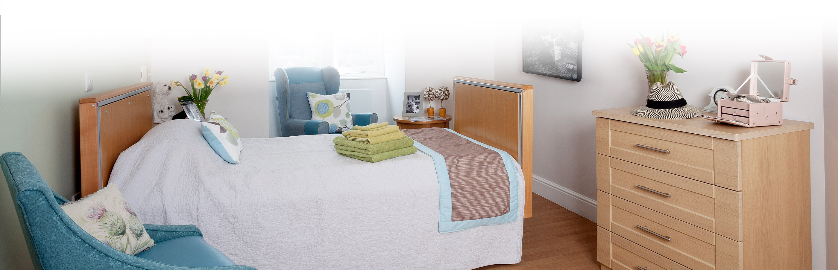 bedroom with bed, tv and stack of draws at Hamilton Nursing Home